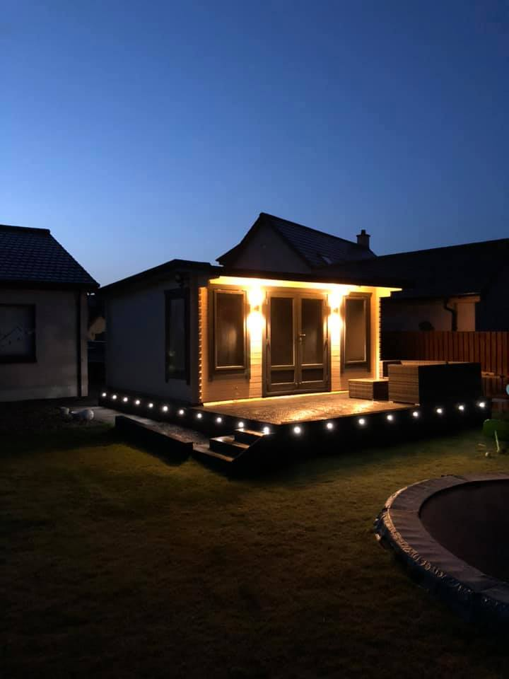 Outside Picture of Log Cabin with Lights at Night